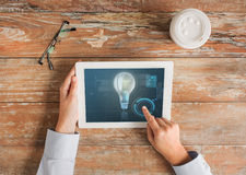Close up of hands with tablet pc and lighting bulb Stock Photo