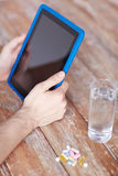 Close up of hands with tablet pc, pills and water Royalty Free Stock Photography