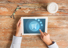 Close up of hands with tablet pc and shopping cart. Business, people, online shopping and technology concept - close up of hands pointing finger to tablet pc Royalty Free Stock Images