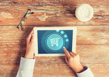 Close up of hands with tablet pc and shopping cart Royalty Free Stock Photography