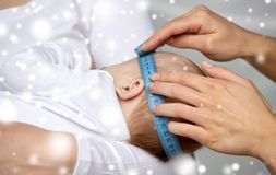 Close up of hands with tape measuring baby head Stock Image
