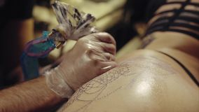 Close-up of hands of tattoo artist in gloves tattooing a pattern on body macro. HD stock video footage
