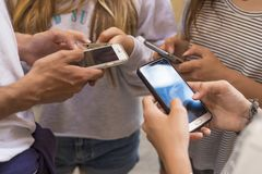 Teens using cell phones. Close up of hands of teens standing outdoors using cell phones Stock Photo