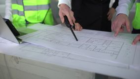 Close up hands of three workers or engineers discussing building drawings in office. Closeup shooting of arms moving