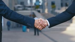 Close up of the hands of top managers in business suits, shake hands with each other, at Business center background stock video footage