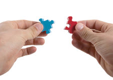 Close-up of hands trying to connect big jigsaw puzzle pieces Royalty Free Stock Image