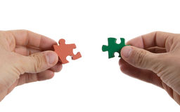 Close-up of hands trying to connect big jigsaw puzzle pieces Royalty Free Stock Images