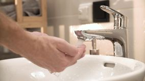 Close Up Of Hands Turn On Running Water In Sink In Bathroom