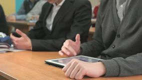 Close-up of hands of two men holding gadgets. Close-up of hands of two men sits at desk at office. One man holding smartphones other man looking at white-black stock video