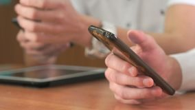 Close-up of hands of two men holding smartphones. Close-up of hands of two unknown men in white shirt sits at desk at office and holding smartphones pressing stock footage