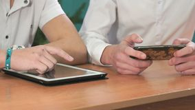 Close-up of hands of two men holding gadgets. Close-up of hands of two men sits at desk at office. One man holding smartphones other man holding white-black stock video