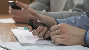 Close-up of hands of two men using smartphones. Close-up of hands of two unknown students dressed in shirt sits at desk at lesson and using black smartphones stock video