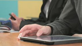 Close-up of hands of two students holding gadgets. Two students sit at desk at office. One man holding smartphones other man looking at white-black computer stock video footage