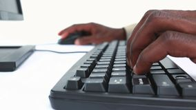 Close up of hands typing on keyboard. Against white background stock video footage