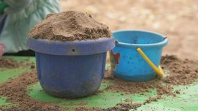 Child filling bucket with sand on table in sandbox. Close-up of hands of unknown child filling bucket with sand on green table in sandbox in an amusement park at stock video