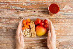 Close up of hands with vegetarian food in box Stock Image