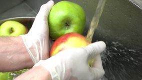 Close up hands washing two apples under tap water. Chef hands washing two fresh apples of different colors stock footage