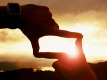 Close up of hands with watch making frame gesture. Dark misty valley bellow in landscape. Stock Photos