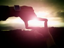 Close up of hands with watch making frame gesture. Dark misty valley bellow in landscape. Stock Images