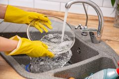 Close up hands of woman washing dishes in kitchen royalty free stock image
