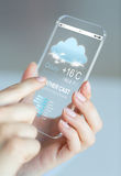 Close up of hands with weather cast on smartphone Royalty Free Stock Images