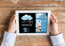 Close up of hands with weather cast on tablet pc Royalty Free Stock Image