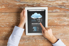 Close up of hands with weather cast on tablet pc Stock Photography