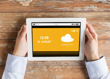Close up of hands with weather cast on tablet pc Stock Photo