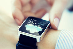 Close up of hands with weather icon on smartwatch Stock Photos