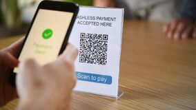 Customer paying with digital money scanning with a smartphone a qr code in a cafeteria.
