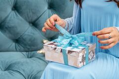 Close-up hands of woman opening gift box on holiday, waiting for desired