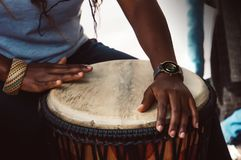 Close up of hands of a woman playing a drum. Nigerian woman playing a traditional African drum stock images