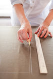 Close up. Hands woman Tailor working cutting a roll of fabric on Stock Image
