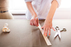 Close up. Hands woman Tailor working cutting a roll of fabric on Royalty Free Stock Photos
