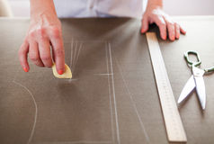 Close up. Hands woman Tailor working cutting a roll of fabric on Royalty Free Stock Photography