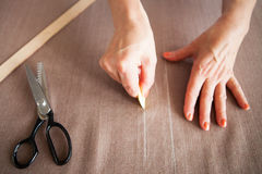 Close up. Hands woman Tailor working cutting a roll of fabric on Royalty Free Stock Images