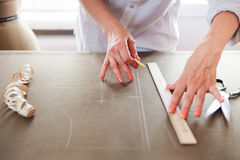 Close up. Hands woman Tailor working cutting a roll of fabric on Royalty Free Stock Image