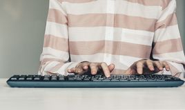 Close-up of hands woman typing on keyboard computer on white table, business concept stock photography