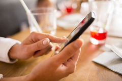 Close up of hands woman using her cell phone in bar Royalty Free Stock Photography