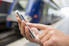 Close up of hands woman using her cell phone at a station platfo Royalty Free Stock Image