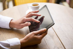 Close up of hands woman using her tablet pc in restaurant Stock Photo