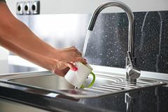 Close up hands of woman washing dishes stock image