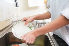 Close up hands of woman washing dishes in kitchen. Close up hands of woman washing dishes in kitchen stock photo