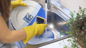 Close up hands of woman washing dishes stock video footage