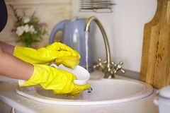 Close up hands of woman wearing yellow gloves washing dishes in kitchen stock images