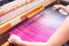 Close up hands of woman weaving purple and white pattern on loom Stock Photography