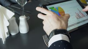 Close up hands of worker discussing business with tablet in cafe. During business lunch. Closeup shooting of arms moving pictures on screen, graphics. Male arm stock footage