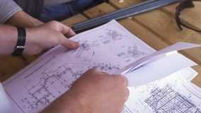 Close up for hands of workers at a factory looking through technical drawings. Blueprints with sketches of projects stock images