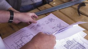 Close up for hands of workers at a factory looking through technical drawings. Blueprints with sketches of projects. Engineering concept stock footage