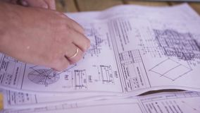 Close up for hands of workers at a factory looking through technical drawings. Blueprints with sketches of projects. Engineering concept stock video footage